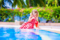 Little girl drinking juice at a swimming pool Stock Image