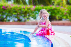 Little girl drinking juice at a swimming pool Stock Images