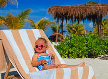Little girl drinking juice on tropical beach Royalty Free Stock Photos
