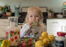 Little girl drinking lemonade from a daisy glass. Little girl drinking fresh squeezed lemonade at the kitchen counter Stock Photo