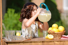 Little girl drinking from lemonade pitcher Royalty Free Stock Photo