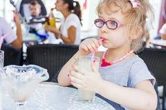 Little girl is drinking lemonade at restaurant. Stock Photos
