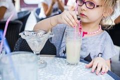 Little girl is drinking lemonade at restaurant. Stock Image