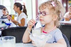 Little girl is drinking lemonade at restaurant. Stock Photography