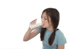Little Girl Drinking Milk 2. Little girl with pig tails in her hair drinking a big glass of cold milk.  Shot isolated on white Royalty Free Stock Photos