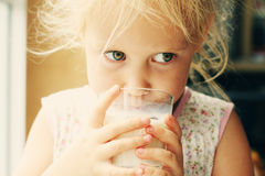 Little girl drinking milk. Cute cheerful little girl drinking milk Stock Photography