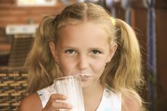 Little girl is drinking milk. Healthy happy Royalty Free Stock Photography