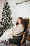 Little girl drinking milk near Christmas tree in morning at home Stock Photography