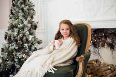 Little girl drinking milk near Christmas tree in morning at home Royalty Free Stock Photography