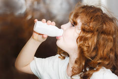 Little girl is drinking for milk or yogurt from bottles. Portrai Stock Photo