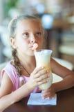 Little girl drinking milkshake Stock Image