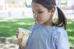 Little girl drinking milkshake at park Stock Image
