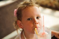 Little girl drinking milkshakes in a cafe outdoors. Little girl drinking milkshakes in a cafe outdoors royalty free stock photos