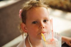 Little girl drinking milkshakes in a cafe outdoors. Little girl drinking milkshakes in a cafe outdoors royalty free stock photography