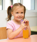 Little girl is drinking orange juice. Cute cheerful little girl is drinking orange juice using straw Stock Photo