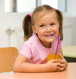 Little girl is drinking orange juice Stock Photo