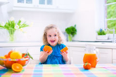 Little girl drinking orange juice. Cute funny little girl drinking freshly squeezed orange juice for healthy breakfast in a white kitchen with window on a sunny Stock Photography