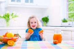 Little girl drinking orange juice Stock Photography