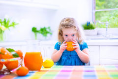 Little girl drinking orange juice. Cute funny little girl drinking freshly squeezed orange juice for healthy breakfast in a white kitchen with window on a sunny Royalty Free Stock Photography
