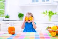 Little girl drinking orange juice Stock Image