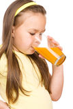 Little girl is drinking orange juice Stock Photos