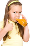 Little girl is drinking orange juice. Isolated over white Stock Photography
