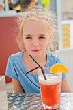 Little girl drinking orange juice Stock Images