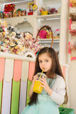 Little girl drinking orange juice through straw Royalty Free Stock Photos