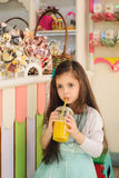 Little girl drinking orange juice through straw Stock Images
