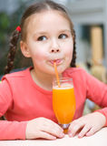 Little girl is drinking orange juice Royalty Free Stock Photos