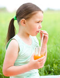 Little girl is drinking orange juice Stock Image
