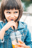 Little girl drinking a smoothie. Funny little girl drinking a fruit smoothie in the street Royalty Free Stock Image