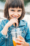 Little girl drinking a smoothie. Happy little girl drinking a fruit smoothie in the street Royalty Free Stock Photo
