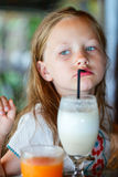 Little girl drinking smoothie outdoors. Adorable little girl drinking fresh smoothie at outdoor cafe on summer day Royalty Free Stock Image