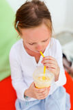 Little girl drinking smoothies outdoors. Adorable little girl drinking fresh smoothies on a colorful pillows at outdoor cafe on summer day Stock Photography