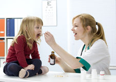 Little girl drinking syrup at lady doctor Royalty Free Stock Images