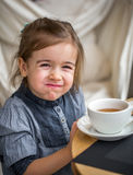 Little girl drinking tea in a cafe Stock Image
