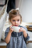 Little girl drinking tea in a cafe Royalty Free Stock Image