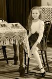 Little girl drinking tea. Cute little girl drinking tea at an antique table with a lace tablecloth.Black-and-white photo. Retro style Stock Photography