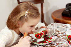 Little girl drinking tea. Cute little girl drinking tea at an antique table with a lace tablecloth.Retro style Stock Photos