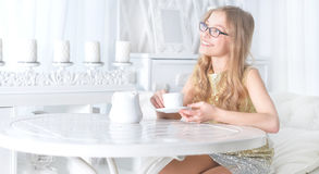 Little girl drinking tea. Little girl in eyeglasses sitting at white table and drinking tea Stock Photo
