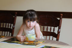 Little girl drinking tea indoors at a table Stock Images
