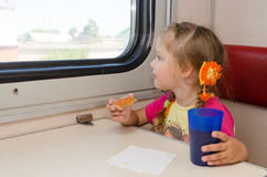Little girl drinking tea with a sandwich on train at the table on outboard second-class carriage and enthusiastically looking Royalty Free Stock Photos