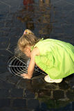 Little girl drinking water. From a public fountain Stock Photos
