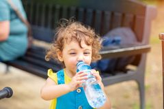 Little girl drinking water from the bottle stock images