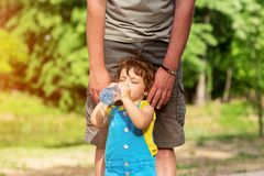 Little girl drinking water from the bottle outdoors royalty free stock photos