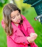 Little girl drinking water in a fountain Royalty Free Stock Photos