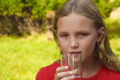 Little girl is drinking water. From a glass in the nature Stock Photography