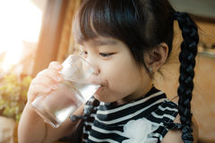 Little girl drinking water. Little girl drinking water in home Royalty Free Stock Photography