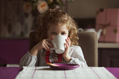 Little girl drinking from a white cup Royalty Free Stock Photos